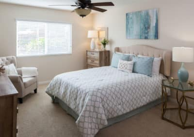 Carpeted bedroom with ceiling fan and natural light